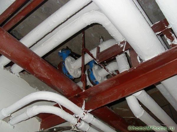 Окрашенные водопроводные трубы в подвале дома