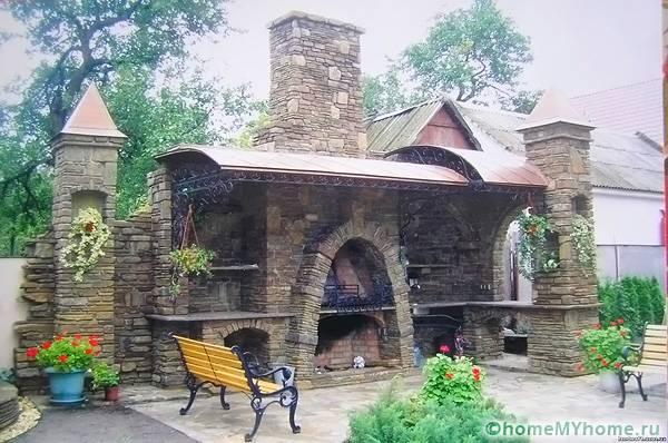Камень в оформлении дачной конструкции соответствует замковому стилю