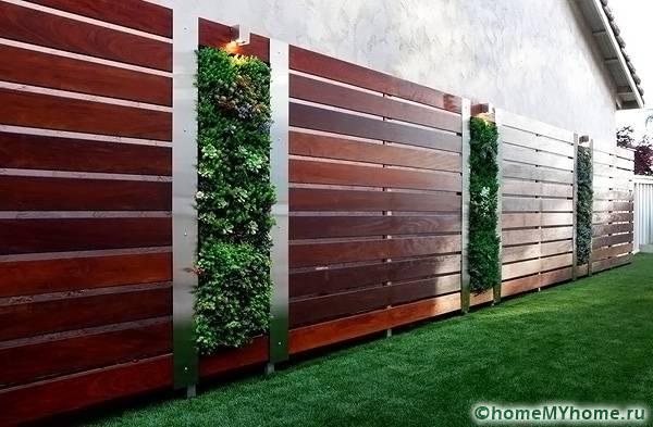 Превратить забор в клумбу помогут цветочные горшки, закрепленные на опорах