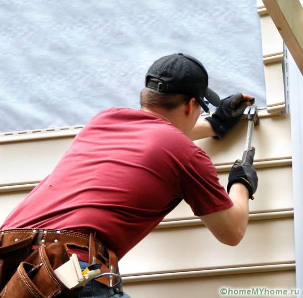 Процесс закрепления панелей на каркасе деревянного дома