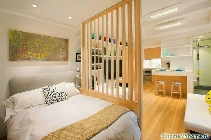В квартире – студии кухню можно отделить от спального места легкой конструкцией, которая не будет загромождать интерьер