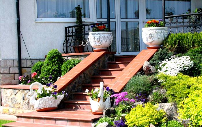 Бетонные ёмкости с цветами могут украсить лестницу на входе в дом
