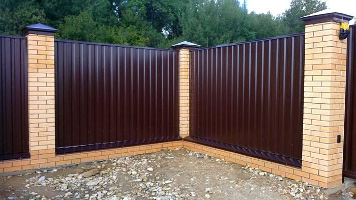 В заборе из профлиста столбы устанавливают с расстоянием в один метр. Особенно привлекательно смотрится сочетание профнастила и кирпичной кладки на столбах