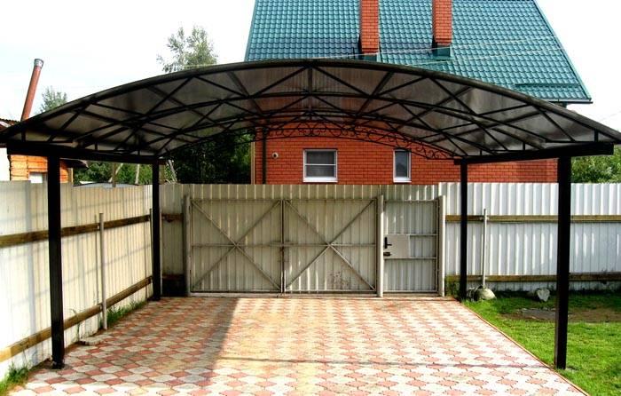 Размещение строения непосредственно около въездной группы помогает экономно использовать свободную площадь. Но такое решение не обеспечивает защиту владельца от дождя и других неблагоприятных атмосферных явлений по пути к дому