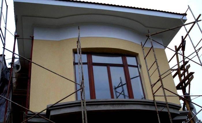 Это фото отделки фасада короедом демонстрирует необходимость применения строительных лесов для безопасного выполнения работ на высоте