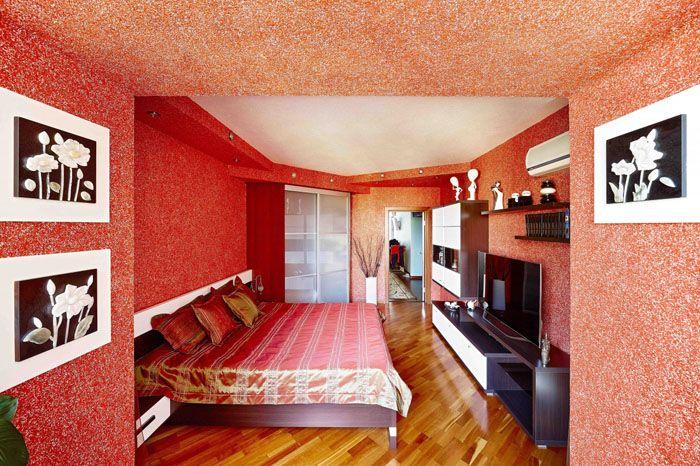 Красный тон стен кого-то раздражает, но в сочетании с тоном мебели и общего декора спальня выглядит милой и чуточку волнующей