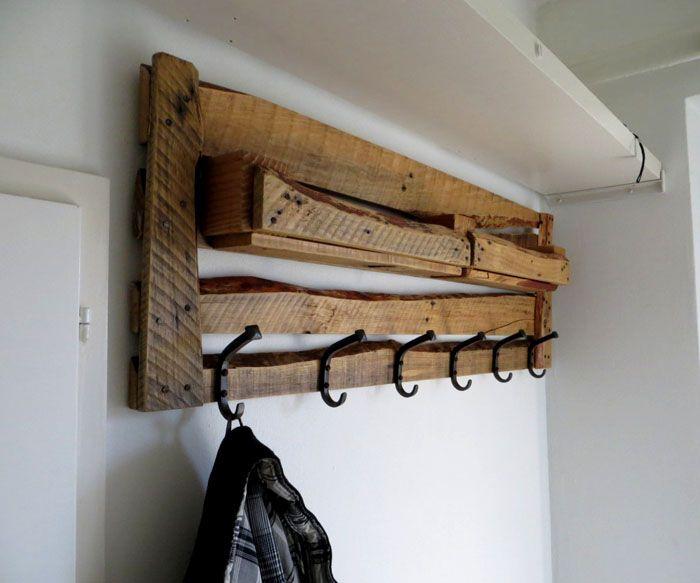 Паллету или её часть крепят к стене, а к дереву прикручивают крючки для одежды