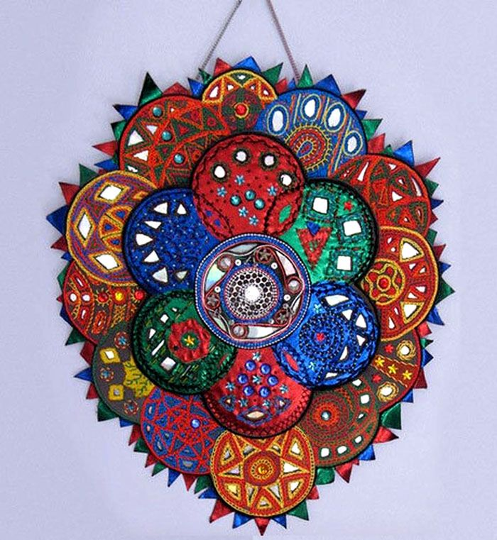 Настенное панно можно сделать, украсив диски яркой тканью, обвязав их или обклеив цветной плёнкой
