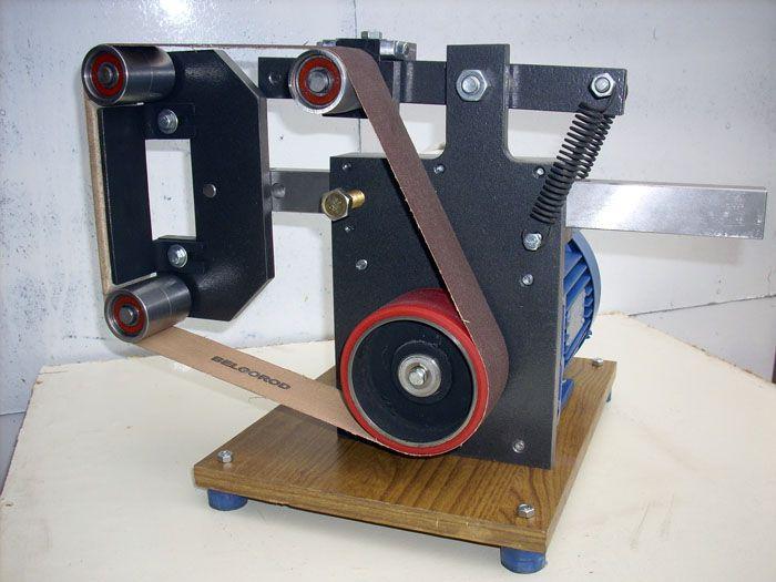 В остальном его конструкция очень схожа с ручной шлифовальной машинкой и имеет в своей основе вращающийся шкив с полосой абразивной бумаги