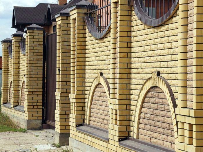 На этом фото показано ограждение дома из жёлтого кирпича. Эффектную контрастную цветовую отделку можно повторить при создании разных архитектурных сооружений на земельном участке