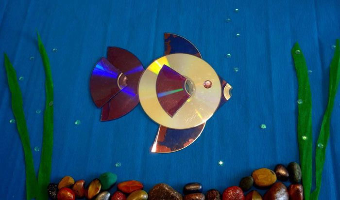 На цветной картон приклеивают диск. С помощью ножниц,цветной бумаги и клея ПВА блестящий кружок превращается в рыбку