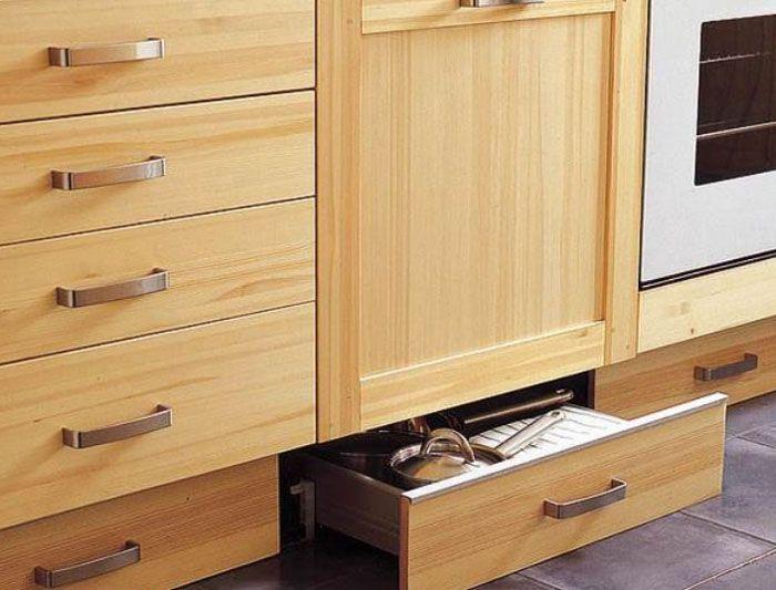 Вместо свободного пространства с заглушками, под основными шкафами устанавливают встроенные ящики на рейлингах