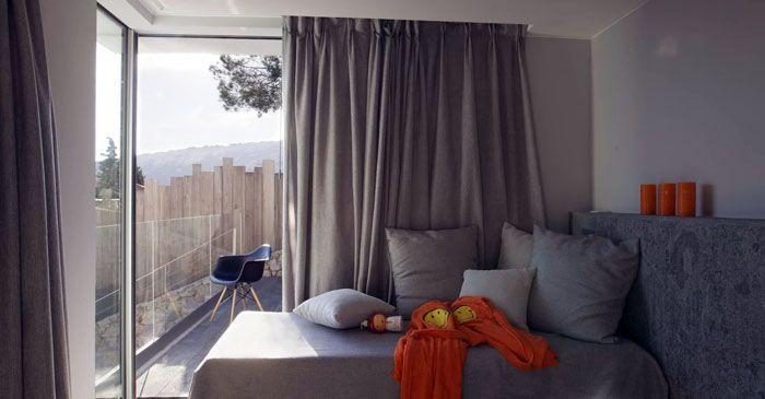 Если центральное место в небольшой комнате занимает кровать, то занавески могут просто доходить до пола
