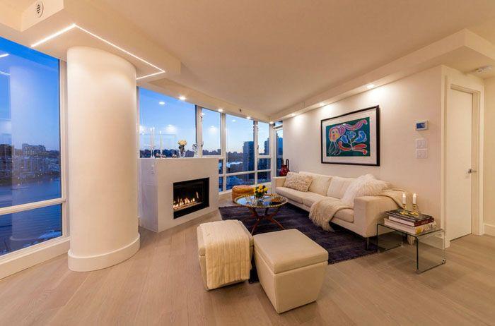 Это фото гостиной комнаты показывает пример удачной маскировки силовой конструкции в квартире. Изменение формы превратило функциональный элемент в оригинальное украшение. Подсветка стыка добавила лёгкость