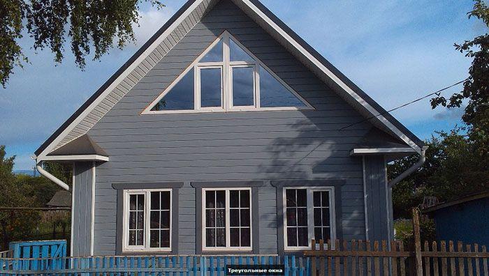Фронтон деревянного дома с установленным в нём витражом из ПВХ-материалов
