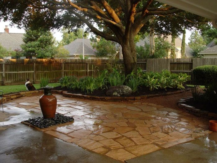 Открытую площадку можно замостить песчаником, кирпичом, срезами деревьев, выложить галькой или просто зацементировать. На фото пластушка во дворе частного дома