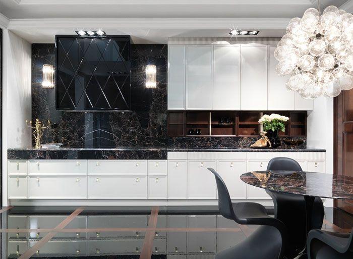 На фото черно-белая кухня в интерьере. Столешница как часть стены созвучна со столом: чёрные агломераты придают интерьеру дорогостоящий и элегантный вид