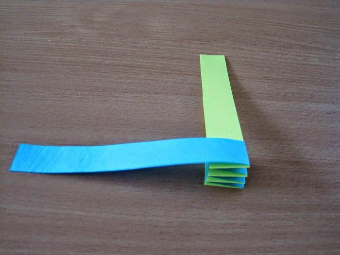 Берём две неширокие и длинные полоски, и накладываем их кончиками перпендикулярно друг другу. Кончики склеиваем ПВА. Начинаем загибать полосы друг на друга. Как только заканчивается полоска, приклеиваем к ней новую