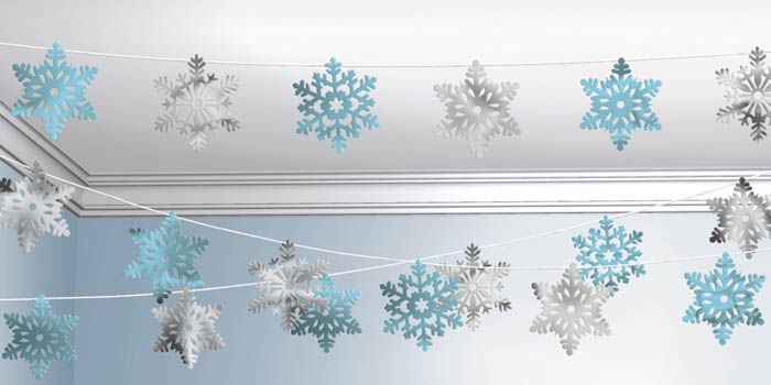 Вырезать снежинки любят практически все, поэтому усаживаем за столь приятное занятие всех, кто прошёл мимо, а сами соединяем снежинки клеем и нитками или по вертикали, или по горизонтали