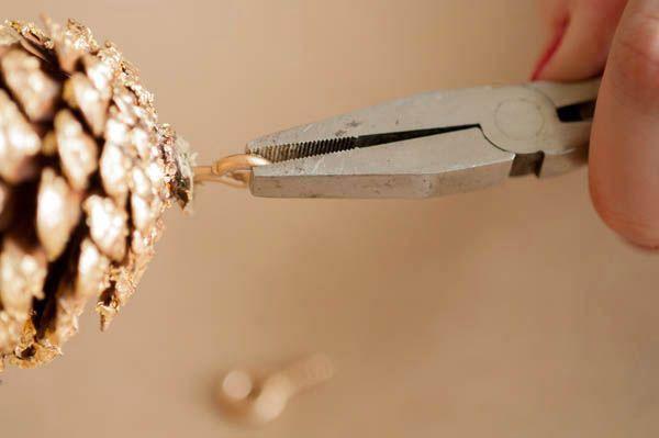 Есть и другой вариант присоединения шишек на верёвку: плоскогубцами несложно вкрутить в шишечку небольшой крючок. Сквозь этот крючок остаётся только пропустить верёвку, и можно сразу вешать украшение