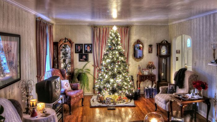 Для традиционных интерьеров остаётся актуальным украсить гостиную внушительной и яркой ёлкой, отвлекающей от прочего в помещении