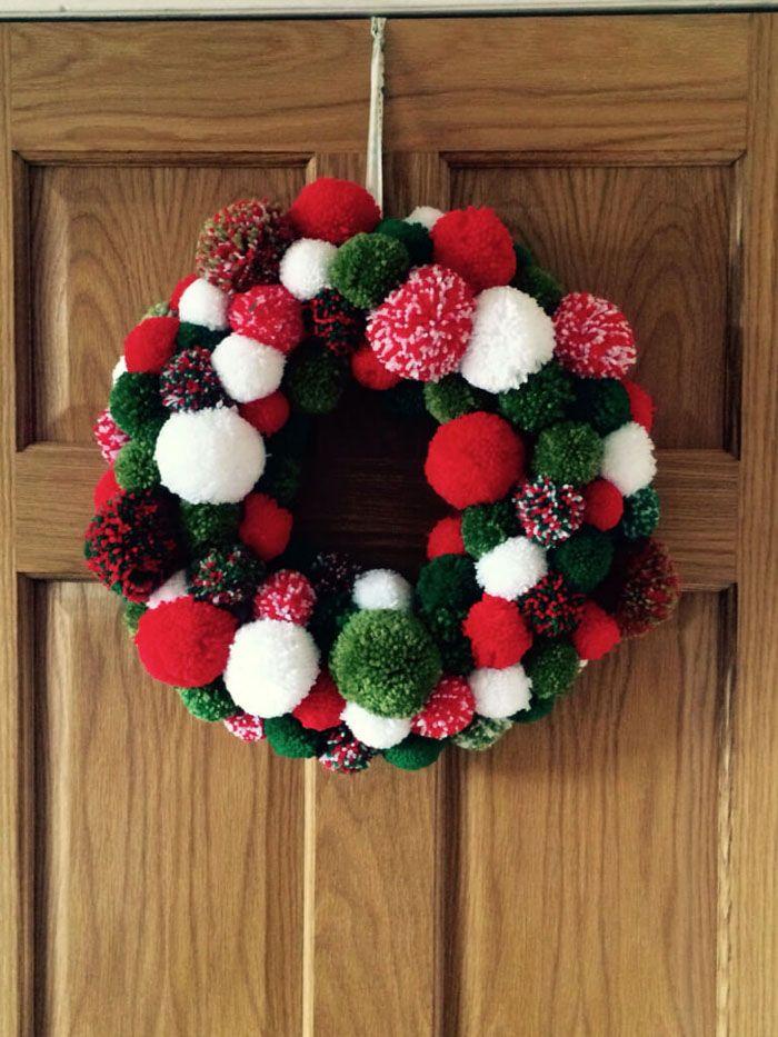Венок из помпонов делают из картонной основы и ниток для вязания. Лучше всего подбирать цвета новогодней тематики: белый, зелёный, красный