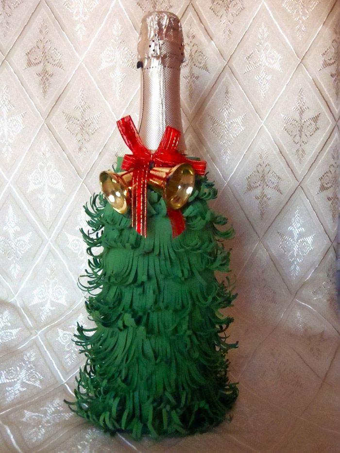 Для такого декора отрезаем от зелёной бумаги длинную полосу и делаем вертикальные частые надрезы не до конца. Начиная с основания бутылки приклеиваем полосу горячим клеем, попутно приподнимая «иголочки» вверх. Верхний край у горлышка декорируют лентой, кружевом, тесьмой, мишурой