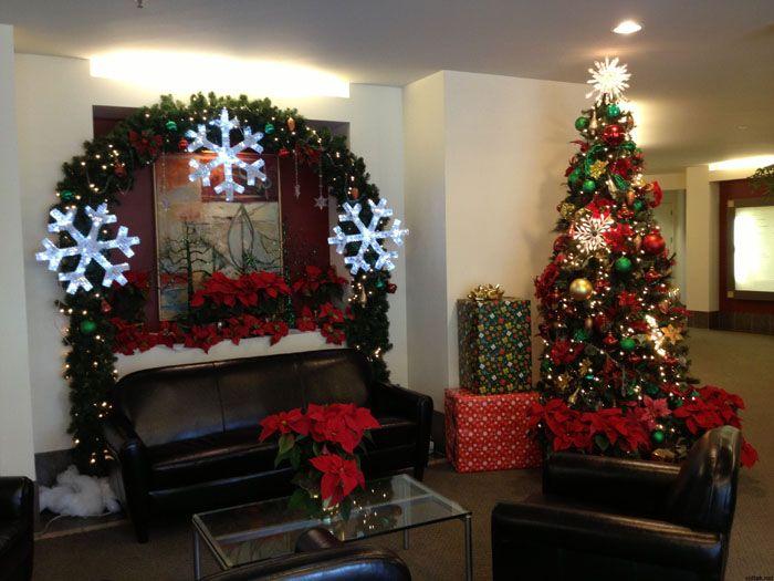Декор в традиционных новогодних цветах. Красивые светодиодные гирлянды и декоративные подарки внушительного размера играют большую роль. Такой подарок делают из коробки из-под офисной техники и обёрточной подарочной бумаги