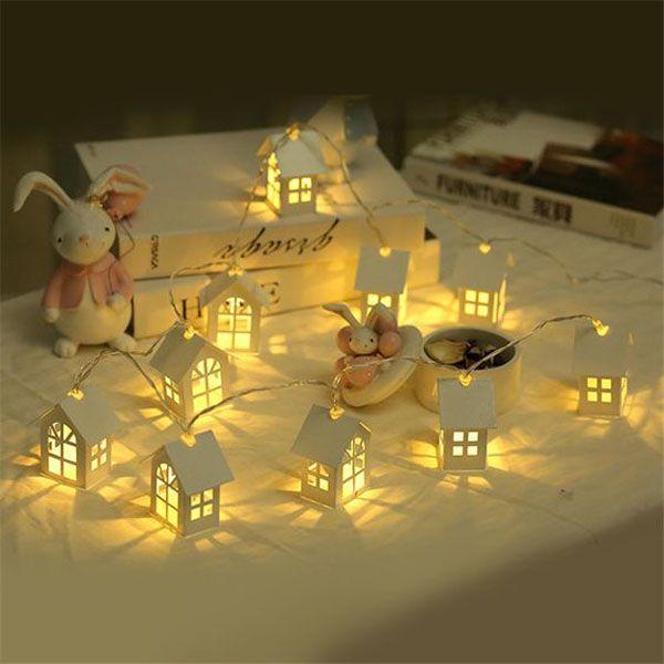 Вырезаем шаблоны домиков из бумаги и собираем их. Внутрь каждого домика пропускаем лампочки от гирлянды. С наступлением каждого вечера у вас в доме будет появляться целый светящийся городок или деревенька