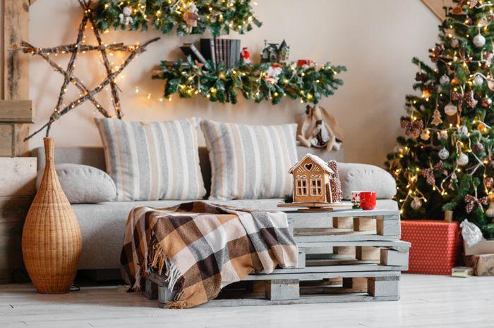 Пледы в клетку — характерное украшение мебели под Новый год. Хвойные гирлянды сами по себе создают нужное настроение