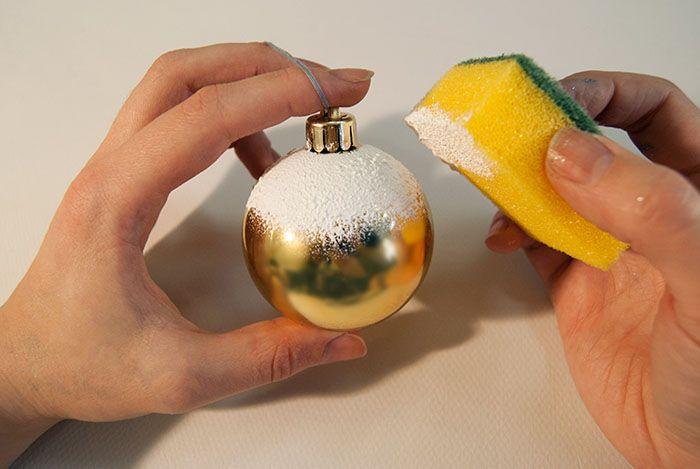 Новогодний шар со снегом получается, если густо обмазать основу клеем ПВА и обвалять в соли и блестках. Вторым способом становится белая акриловая краска: ее наносят губкой на игрушку