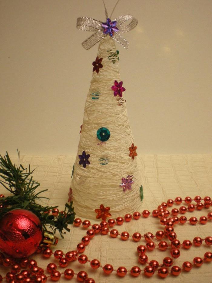 Белые нитки символизируют заснеженное деревце, которое нетрудно украсить любым материалом!