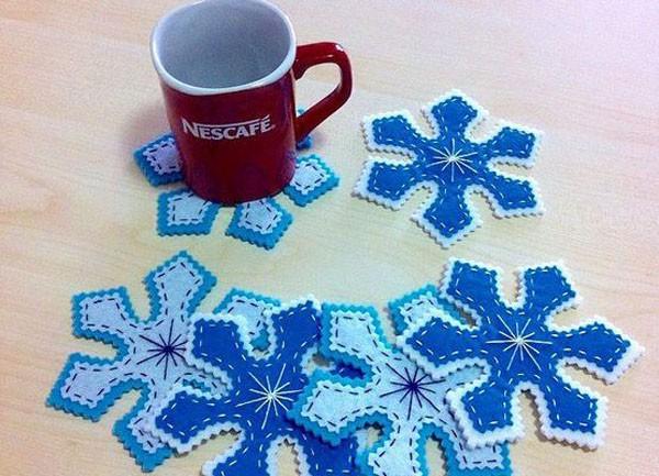 Вырезаем шаблон снежинок, один делаем меньше. Сначала декорируем снежинку меньшего размера вышивкой, а затем сшиваем их, наложив друг на друга и выровняв по центру