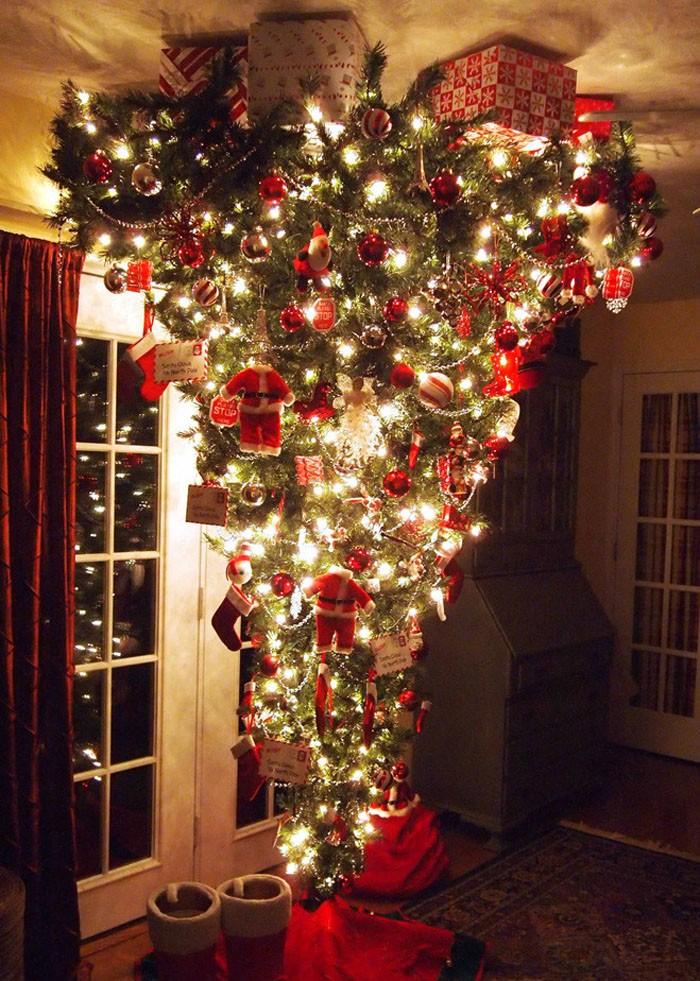 Можно расположить ёлку кверху ногами от потолка до пола, на потолке разместить декоративные подарки
