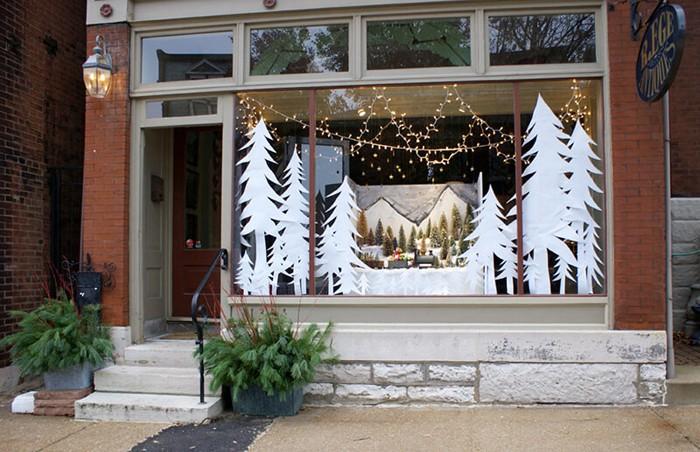 Вход в небольшой магазин можно сделать красивее, если разместить в неиспользуемых зимой цветочных клумбах ветки хвои