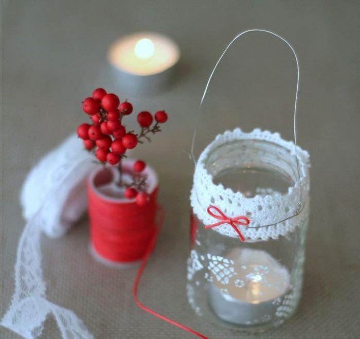 Маленькие баночки из стекла становятся удобным пристанищем для небольшой плоской свечи. Нужно только задекорировать край банки