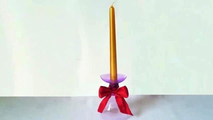 Чтобы сделать такой подсвечник своими руками для высоких свечей, берут две пластиковых бутылки. У одной отрезают горлышко меньше, у второй больше. Два горлышка соединяют друг с другом горячим клеем, затем устанавливают поделку на широкое основание, а в узкое вставляют свечу. Один красивый бант, и можно любоваться изделием!