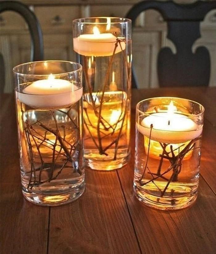 Высокие бокалы и веточки деревьев, вода и свечка, и результатом такого совмещения будет красота, которую можно разместить на праздничном столе или использовать как одиночную композицию