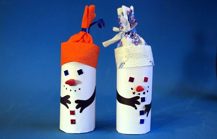 Втулка от салфеток способна превратиться в снежного гостя лёгким мановением руки: оклеиваем втулку белой бумагой, методом аппликации создаём лицо и ручки. Салфетка складывается в очаровательный зимний головной убор