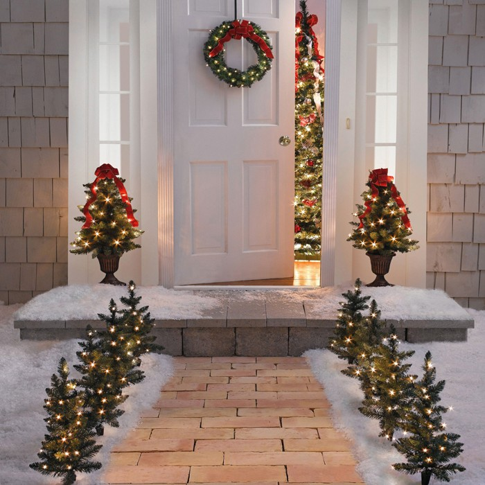Крыльцо снаружи украшают чем угодно: это могут быть и ветки хвои, декорированные электрической гирляндой или игрушками