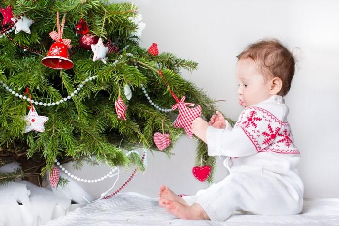 При установке хвойного дерева в помещении с ребёнком учитывают устойчивость и шаткость ёлки. Даже если кроха потянет за нижние ветки ручками, ёлочка не должна на него упасть. А что пальчик уколется, это нестрашно!