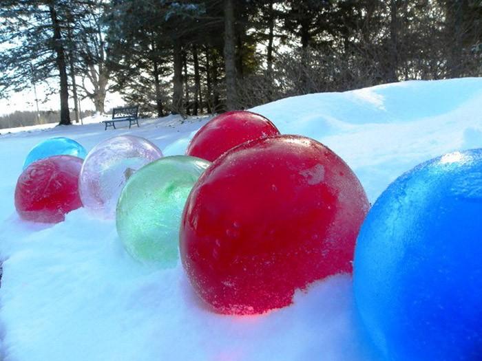 Наливаем в шарик окрашенную воду и оставляем замерзать. Разрываем оболочку шарика и являем миру яркую ледовую игрушку большого размера
