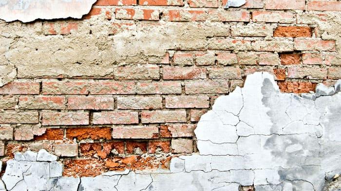 Пример плохой адгезии штукатурки к кирпичной стене