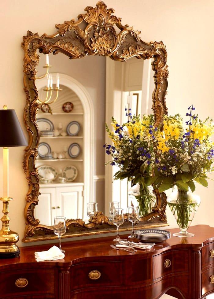 Массивные позолоченные рамы больших зеркал утяжеляют пространство, создавая визуальное равновесие между мебелью и отделкой стен. На тумбочку около зеркала всегда можно поставить свежие цветы в шикарной вазе