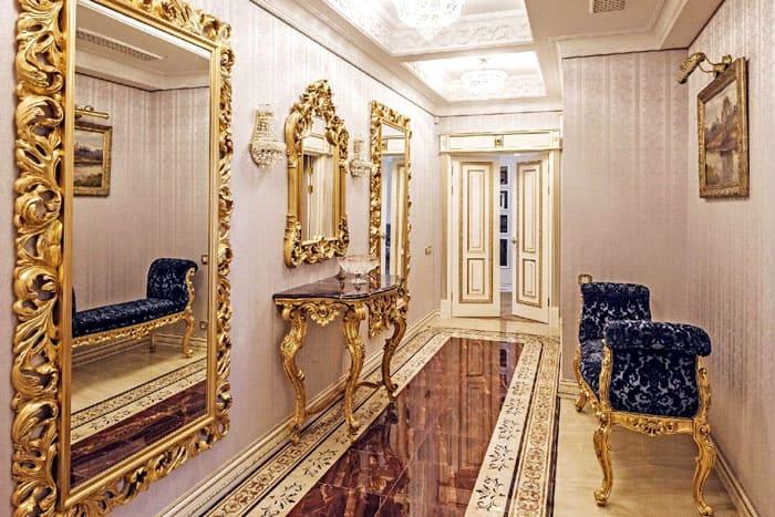 Интерьер дорогой во всём: от широких огромных зеркал и позолоченных рамах до кушетки. Отделка стен в прихожей может быть менее щегольской, но часто с блестящим полом и украшенным лепниной или карнизами потолком