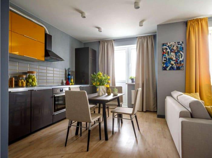 Часть помещения-студии зонирована мебелью и цветом: цвет штор и разделяет пространство, и объединяет, так как этот же оттенок использован в кухонном гарнитуре