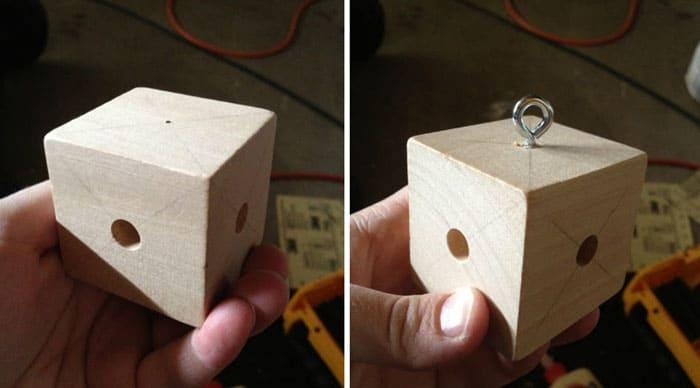 Из деревянного куба и металлического крюка делают держатель для игрушек. В кубе просверливают 4 отверстия, в которые вставляют палочки. На палочках развешивают игрушки, а крюк крепится к каркасу изделия