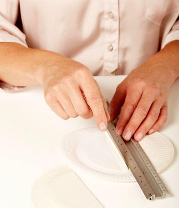 В центре каждой тарелки нужно прочертить две параллельных линии по 0,5 – 1 см друг от друга. По этим линиям складываем тарелку пополам, получив по центру полосу для наклеивания