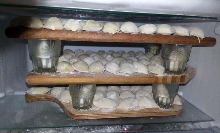 Заморозить много пельменей можно, сделав в морозилке ярусы с помощью кружек или баночек