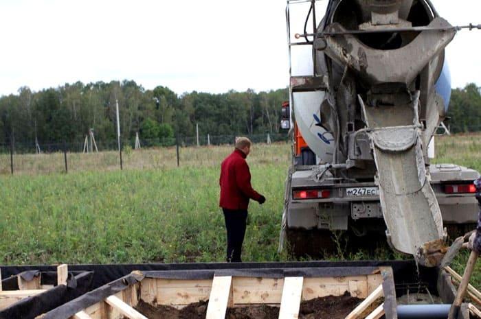 Процесс заливки бетона в заранее подготовленную и гидроизолированную ёмкость из дерева